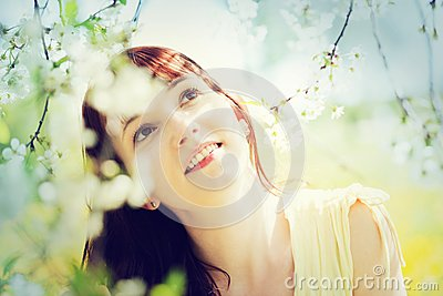 Natural, beautiful woman relaxing and smiling in a spring garden. Stock Photo
