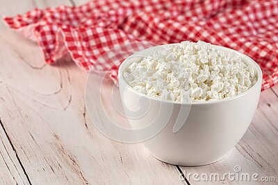 Natural cottage cheese in a white ceramic bowl with wooden spoon and red napkin on a wooden background. Diet concept. Natural cottage cheese in a white ceramic stock images