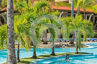 Natural fluffy palm tree garden with little girl swimming in the pool