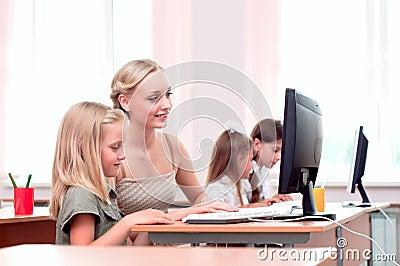 Nauczyciel wyjaśnia zadanie przy comput