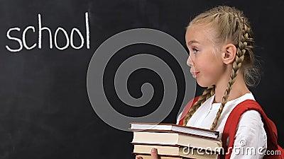Naughty girl met boeken zonder gebaar, schoolwoord op schoolbord stock footage
