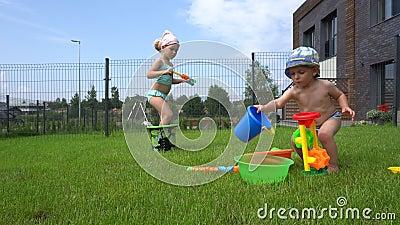Naughty girl schiet op haar broertje met het speelgoedwaterpistool en hij rent weg stock footage