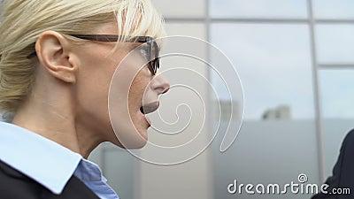 Naughty mannelijke baas flirt met geschokt vrouwelijke werknemer in de buurt van kantoor, pesterijen stock footage