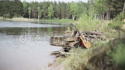 nave De vergeten gitaar op de bank van het meer stock videobeelden