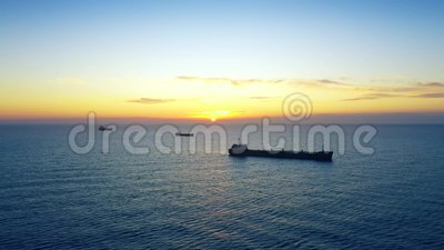 Navios de carga ao largo da costa em nascer do sol ou pôr do sol no mar filme