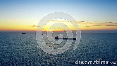 Navios de carga ao largo da costa em nascer do sol ou pôr do sol no mar vídeos de arquivo