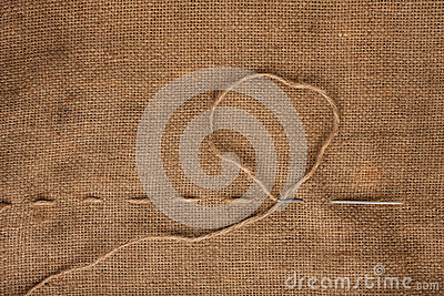 Needle and thread on burlap background
