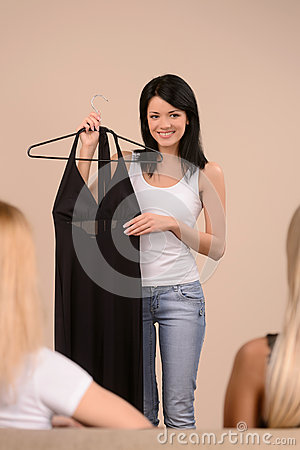 She needs an advice. Beautiful young woman showing a dress to he