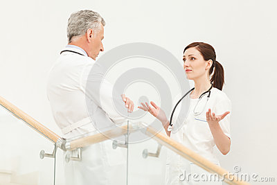 She needs a professional advice. Mature doctor listening to his