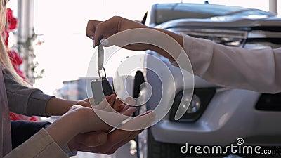 Negocio automovilístico, manos de la familia de coche de los dueños tomar llaves en el fondo del primer del automóvil en centro d almacen de metraje de vídeo