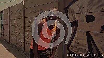 negro cansado y agotado corredor profesional norteamericano sin aliento después de un duro ejercicio urbano parado enfriándose almacen de video