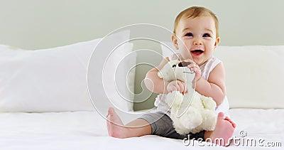 Neonata sveglia che gioca con il giocattolo molle sul letto video d archivio