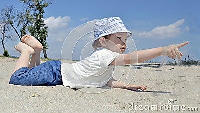 Neonato che gioca in sabbia sulla spiaggia