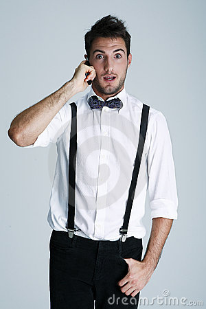 Nerdy young man in suspenders on the phone