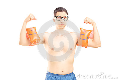 Nerdy young man with swimming arm bands showing his muscles