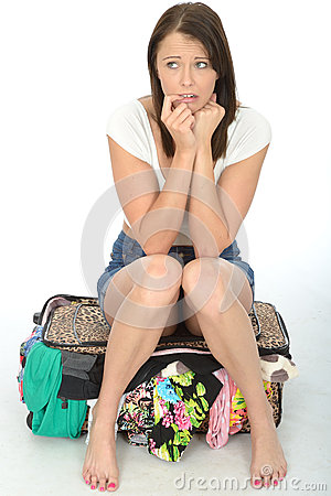 Free Nervous Anxious Attractive Young Woman Sitting On An Overflowing Suitcase Royalty Free Stock Photos - 53536198