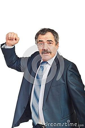 Nervous mature businessman showing fist