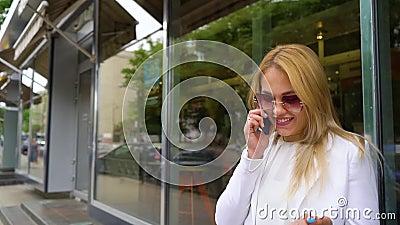 Nette Blondine in der modernen Ausstattung sprechend am Telefon auf der Straße stock video footage