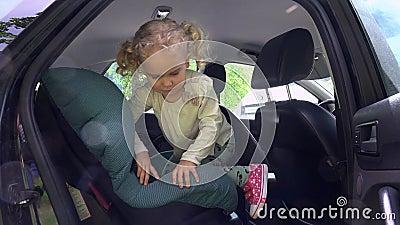 Netter Aufstieg des kleinen Mädchens und sitzen im Kindersitzstuhl und bewegen Hand wellenartig stock video footage
