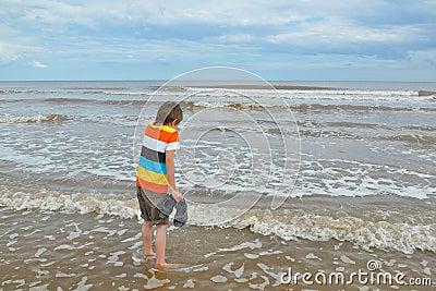 Netter kleiner Junge in den Wellen auf Strand, kaltes Wasser