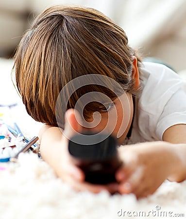 Netter kleiner Junge, der Fernsieht, auf dem Fußboden zu liegen