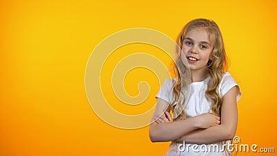 Nettes jugendlich Mädchen lokalisiert auf dem orange Hintergrund, der Daumen-oben Geste, Schablone zeigt stock footage