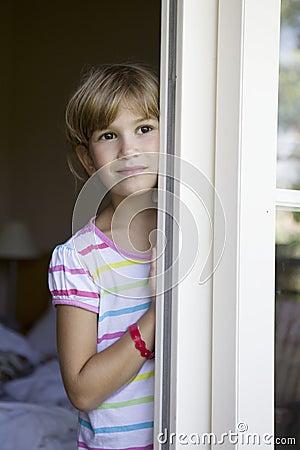Nettes lächelndes Mädchen, das Verstecken spielt