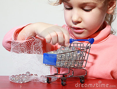 Nettes Mädchensorgfaltspiel mit Spielzeugeinkaufenlaufkatze