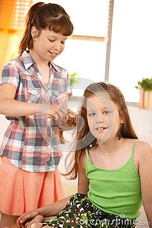 Nettes Mädchen, das Haar des Freunds kämmt