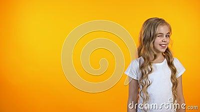 Nettes Schulmädchenblinzeln lokalisiert auf orange Hintergrund, wenig Kokette, Schablone stock video