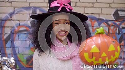 Nettes schwarzes jugendlich Mädchen im Hexenhut, der Gesichter auf Halloween aufwirft stock video footage