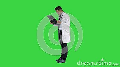 Neurocirurgião observando a varredura de MRI, progresso de exame da doença em uma tela verde, chave do croma filme