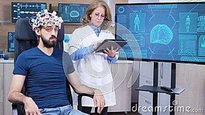 Neurologe bei Weibchen, die Daten aus dem GehirnwellenscannerHeadset lesen stock video