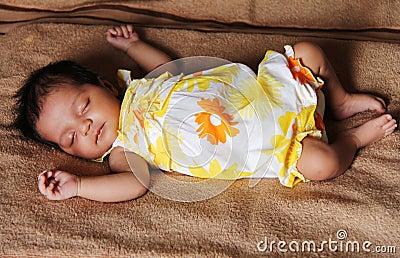 New born asian baby girl sleeping in cute dress