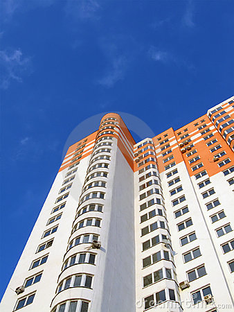 New colorful orange building, blue sky, clouds