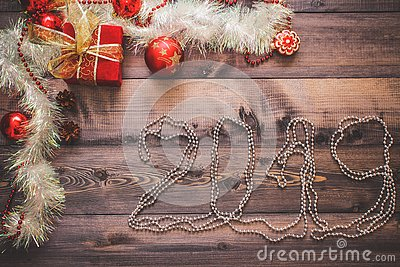 New Year`s decor and festive toys on a wooden table with a red string box with a gift Santa Claus.New Year 2019 lined festoons Stock Photo