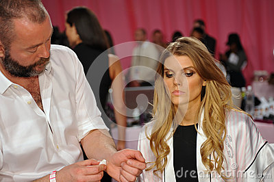 NEW YORK, NY - NOVEMBER 13: Makeup Artist Dick Page applying make-up to Maryna Linchuk at the 2013 Victoria s Secret Fashion Show Editorial Stock Photo