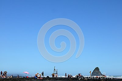 New Zealand: holiday-makers on black sand beach Editorial Stock Image