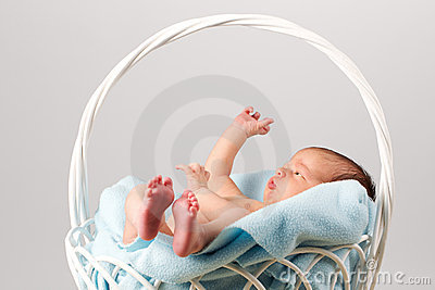 Newborn Baby in a blanket-lined basket.