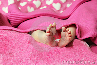 Newborn baby clutching mothers finger