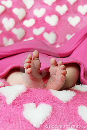 Newborn baby clutching mothers finger