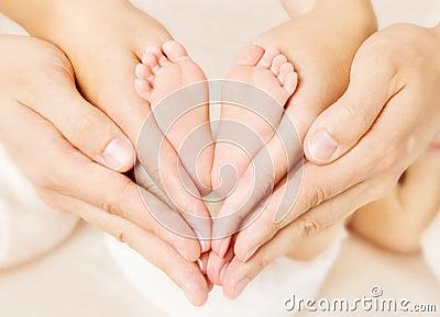 Newborn baby feet parents holding in hands.