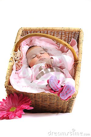Newborn baby girl in a basket, white beads