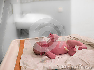 A newborn baby girl cries moments after birth