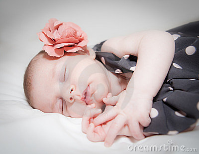 Newborn baby girl with flower sleeping