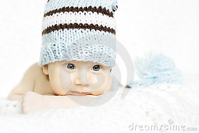 Newborn baby portrait in blue woolen hat close up