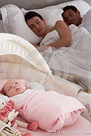 Newborn Baby Sleeping In Cot In Parents Bedroom
