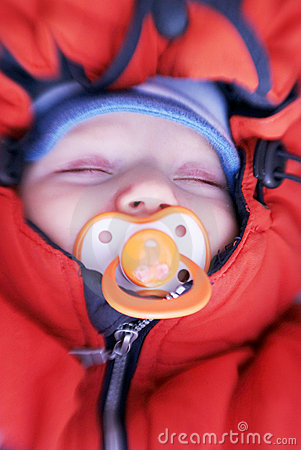 Newborn baby with soother in winter clothes