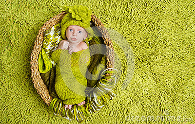 Newborn baby in woolen green hat inside basket