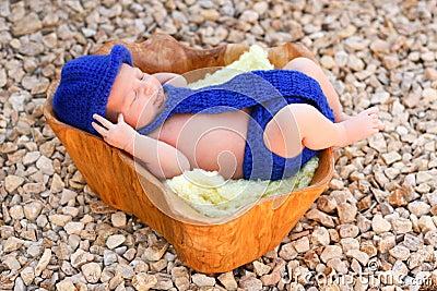 Newborn boy wearing blue fedora, tie, diaper cover